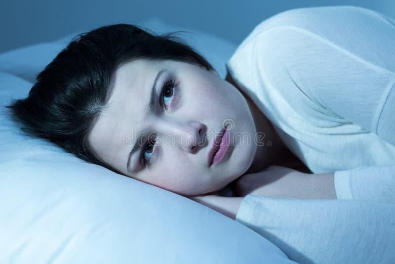 Ongerust gemaakt meisje in bed stock fotografie