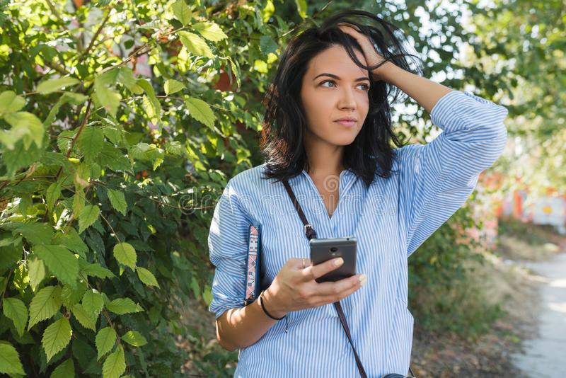 Ongerust gemaakt modieus Kaukasisch studentenmeisje die haar collega's op de straat wachten die online communicatie met vrije rad royalty-vrije stock afbeelding