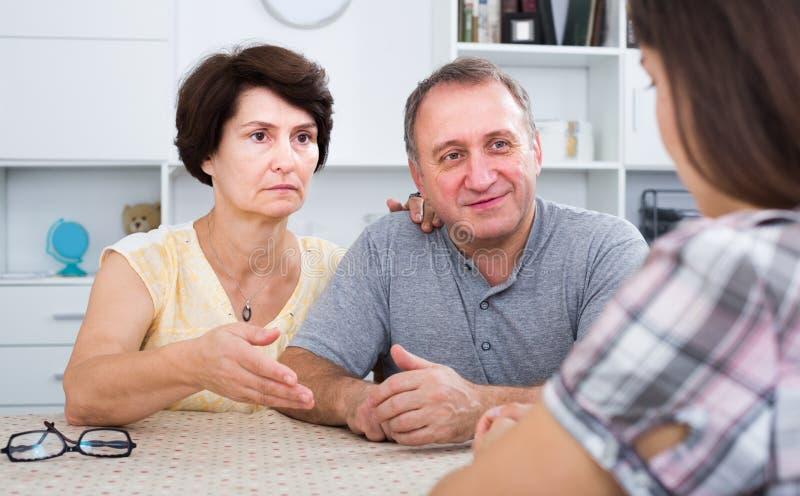 Ongerust gemaakt rijp familiepaar die aan jonge vrouw luisteren stock afbeeldingen