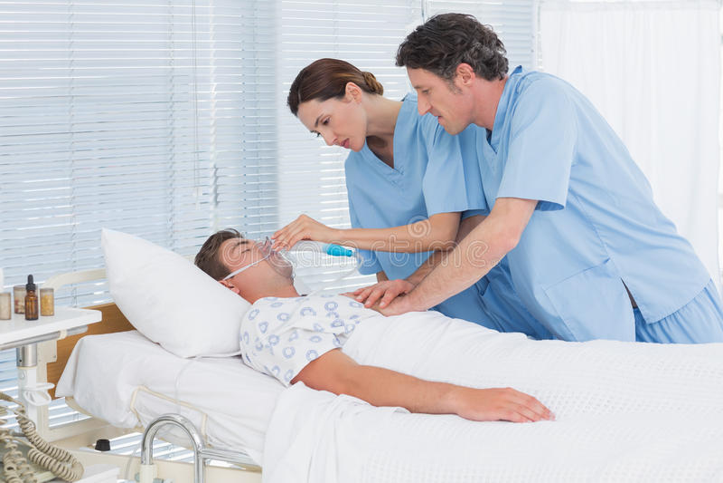 Ongerust gemaakte artsen die hartmassage doen en zuurstofmasker houden royalty-vrije stock foto