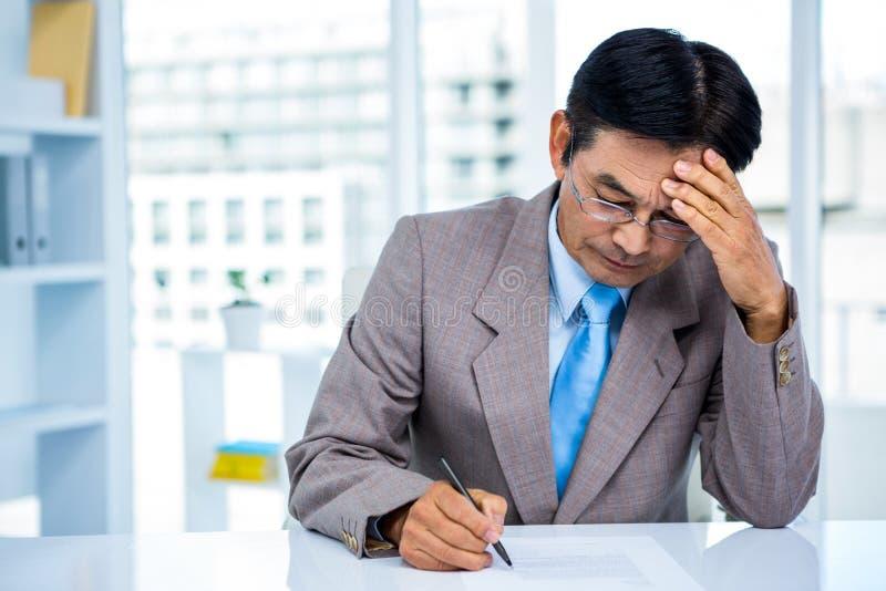 Ongerust gemaakte Aziatische zakenman op zijn bureau royalty-vrije stock afbeeldingen