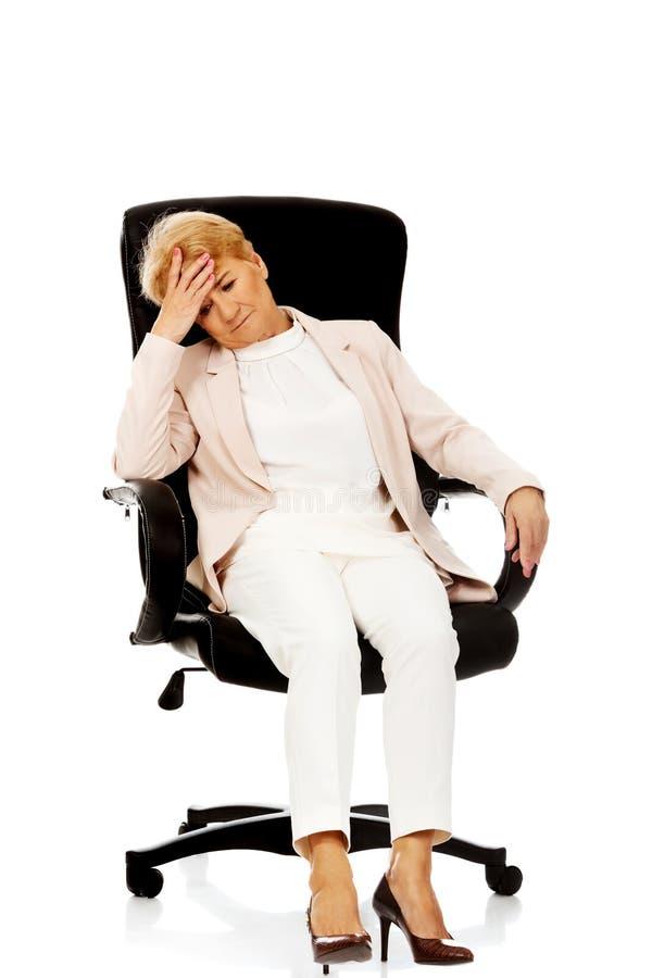 Ongerust gemaakte bejaarde bedrijfsvrouwenzitting op leunstoel royalty-vrije stock foto's