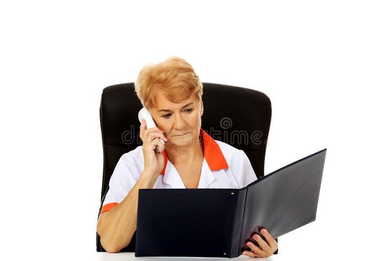 Ongerust gemaakte bejaarde vrouwelijke arts of verpleegster zitting achter het bureau en het spreken door een telefoon stock afbeeldingen