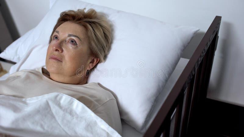 Ongerust gemaakte bejaarde in ziekbed liggen en pati?nt die, alzheimersziekte rond kijken stock foto's