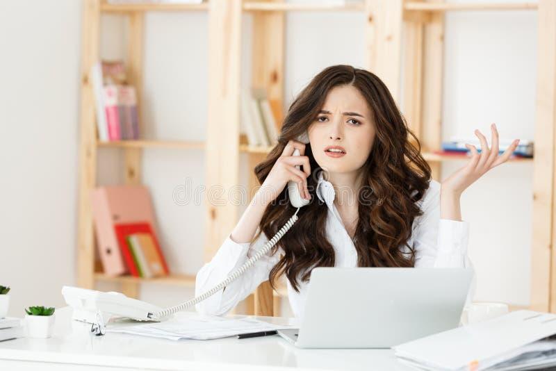 Ongerust gemaakte beklemtoonde gedeprimeerde beambte bedrijfsvrouw die het slechte telefoongesprek van de nieuwsnoodsituatie ontv stock foto