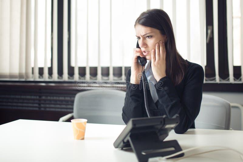 Ongerust gemaakte beklemtoonde gedeprimeerde beambte bedrijfsvrouw die het slechte telefoongesprek van de nieuwsnoodsituatie ontv stock fotografie
