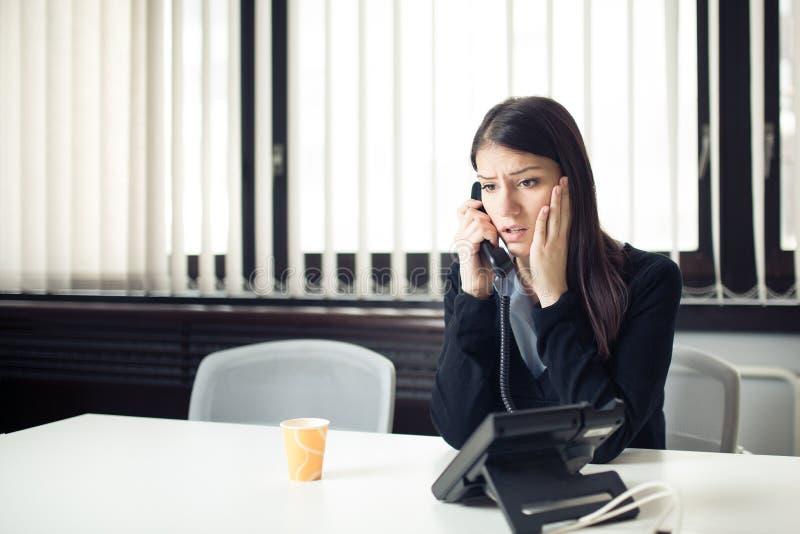 Ongerust gemaakte beklemtoonde gedeprimeerde beambte bedrijfsvrouw die het slechte telefoongesprek van de nieuwsnoodsituatie ontv royalty-vrije stock afbeelding