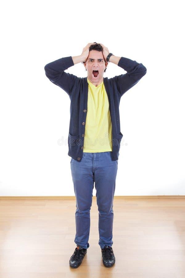 Ongerust gemaakte beklemtoonde mens die met handen op zijn hoofd gillen stock fotografie