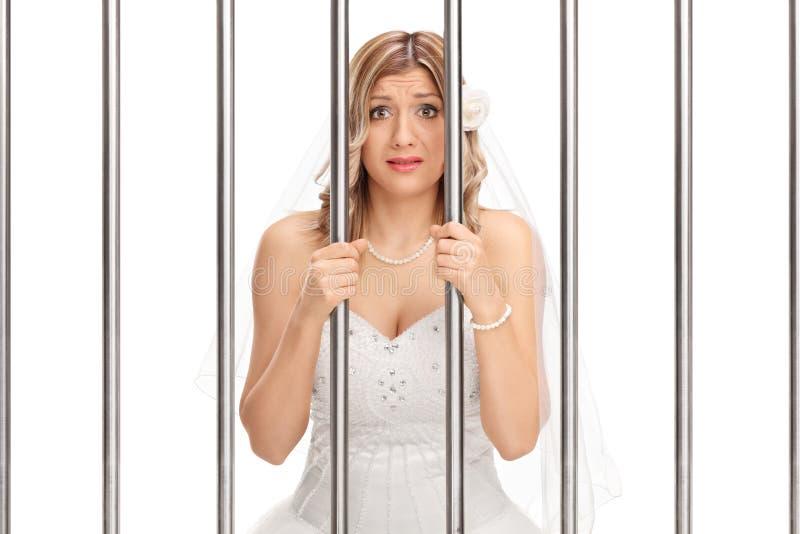 Ongerust gemaakte bruid die zich achter de tralies in gevangenis bevinden royalty-vrije stock fotografie
