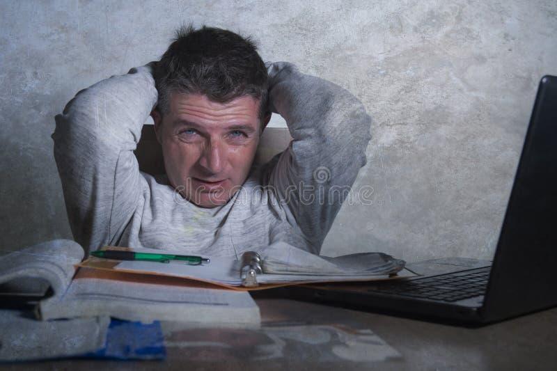 Ongerust gemaakte en wanhopige mens die laat werken - het nacht thuis bureau met laptop computergevoel frustreerde en vermoeide b royalty-vrije stock foto