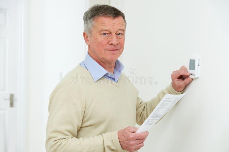 Ongerust gemaakte Hogere Mens met Bill Turning Down Heating Thermostat royalty-vrije stock afbeelding