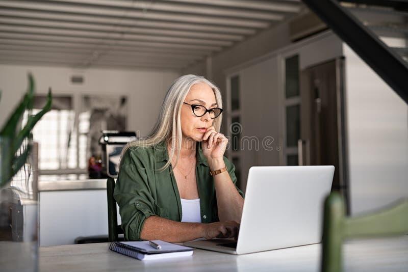 Ongerust gemaakte hogere vrouw die laptop met behulp van stock foto's