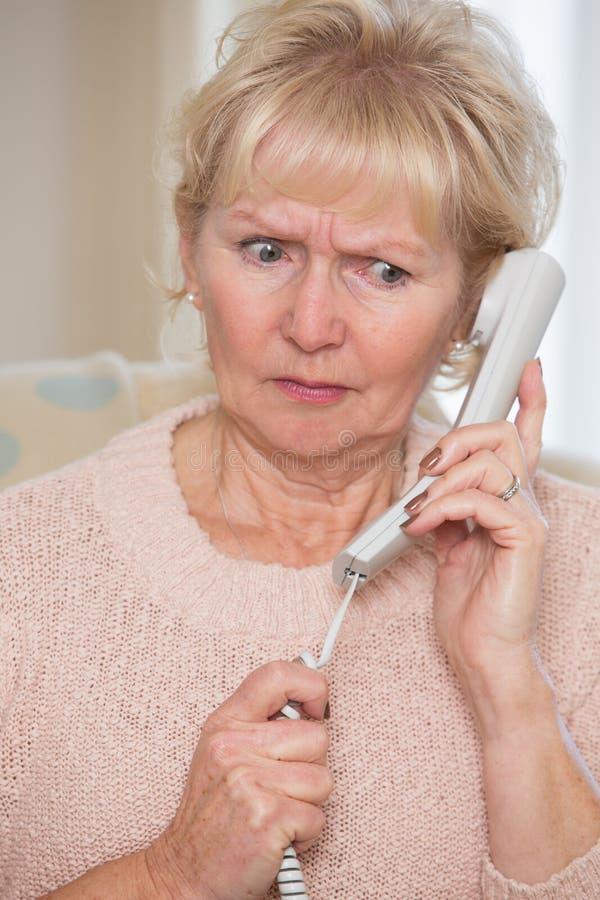 Ongerust gemaakte Hogere Vrouw die Telefoon thuis beantwoorden royalty-vrije stock foto's