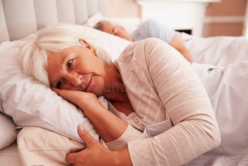 Ongerust gemaakte Hogere Vrouw die Wakker in Bed liggen stock foto's