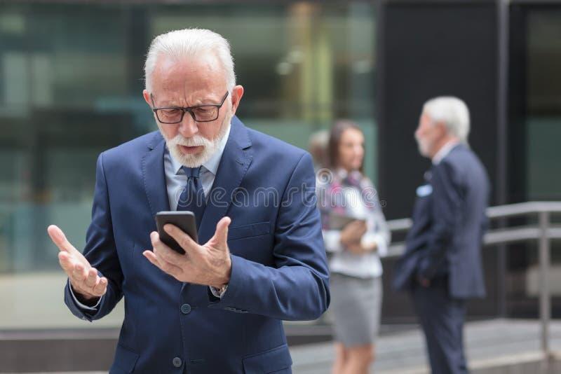 Ongerust gemaakte hogere zakenman die smartphone voor een bureaugebouw met behulp van stock afbeeldingen