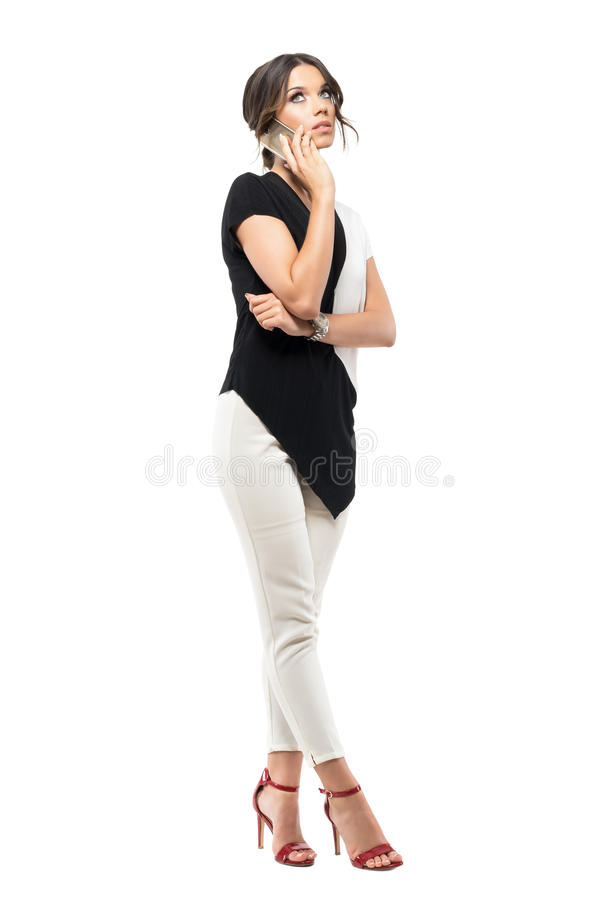 Ongerust gemaakte jonge bedrijfsvrouw in modieus kostuum die op de mobiele telefoon spreken die omhoog eruit zien royalty-vrije stock fotografie