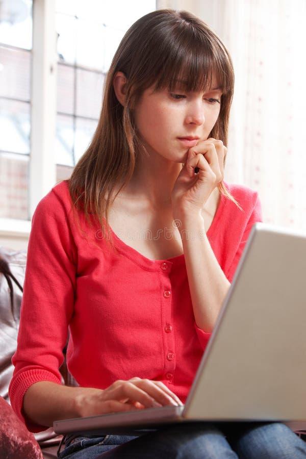 Ongerust gemaakte Jonge Vrouw die Laptop thuis met behulp van royalty-vrije stock afbeeldingen