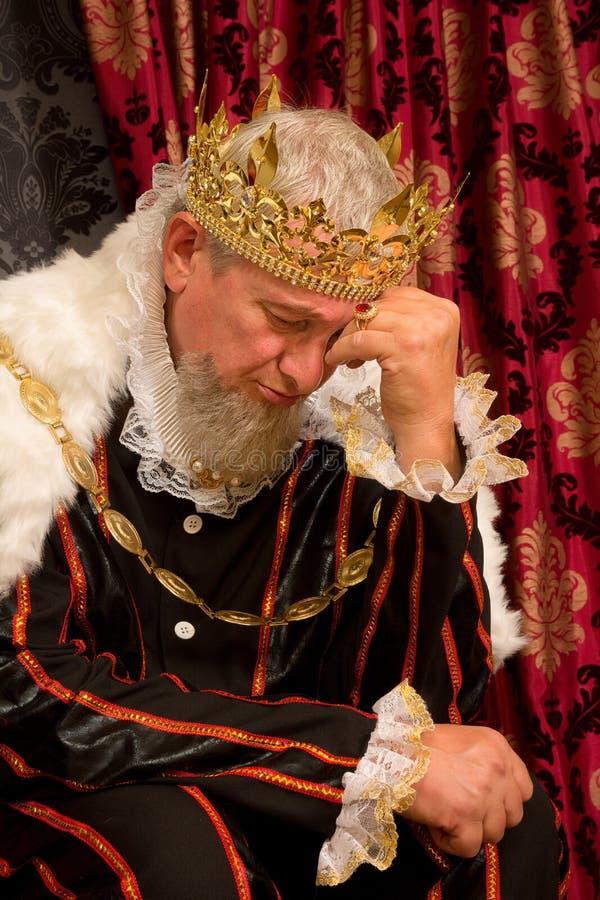 Ongerust gemaakte koning op troon stock foto's