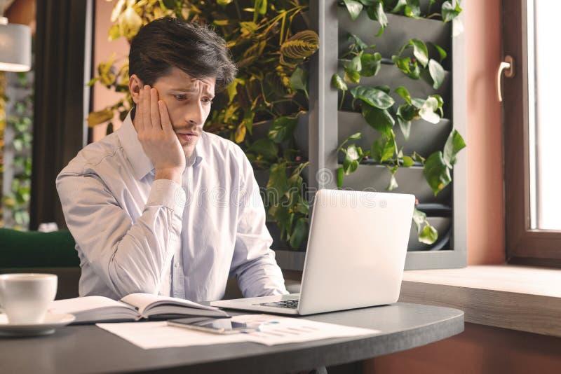 Ongerust gemaakte mens die slecht financieel nieuws online in koffie lezen royalty-vrije stock afbeelding