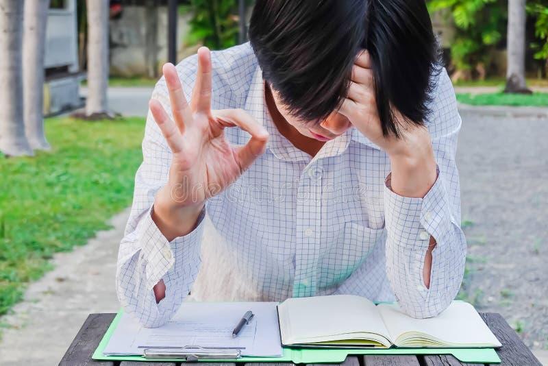 Ongerust gemaakte mens die slecht nieuws in een boek maar zijn tonend o.k. gebaar op vakantie in het park lezen royalty-vrije stock fotografie