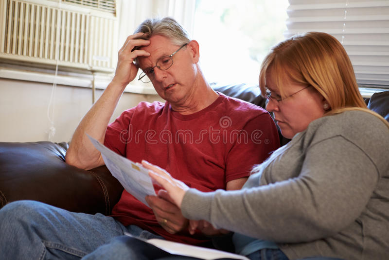 Ongerust gemaakte Paarzitting op Sofa Looking At Bills royalty-vrije stock afbeelding