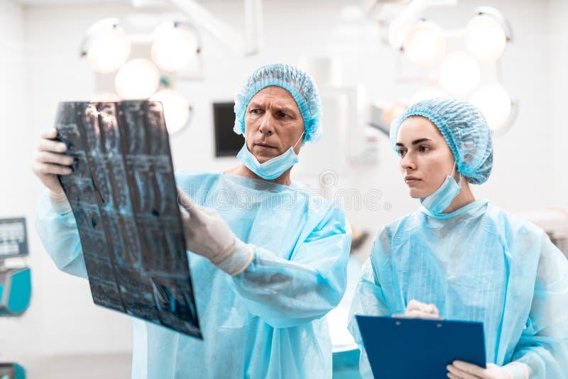 Ongerust gemaakte specialisten die de het x-ray resultaten en fronsen bekijken stock fotografie