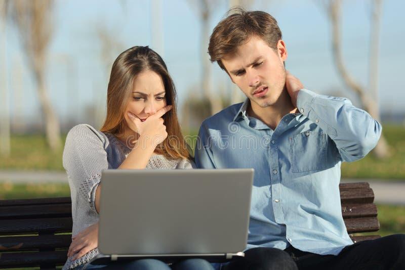 Ongerust gemaakte studenten of ondernemers die op laptop in openlucht letten royalty-vrije stock afbeeldingen