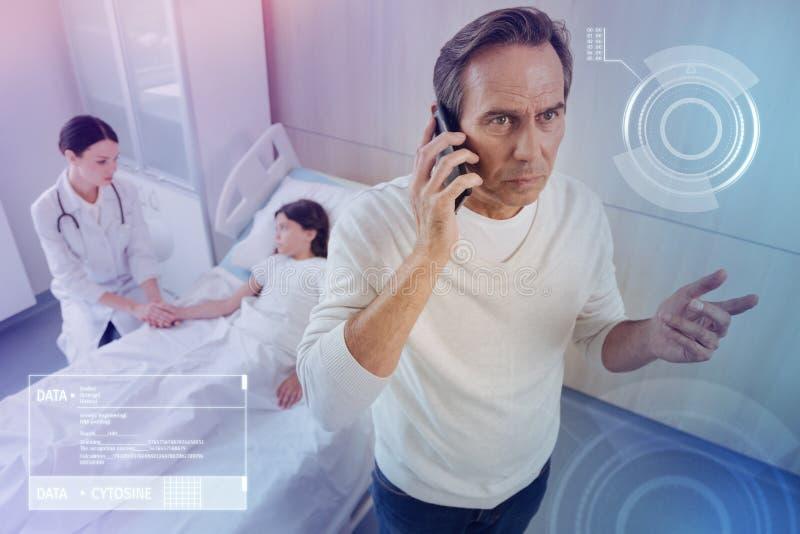 Ongerust gemaakte vader die een telefoonbespreking hebben terwijl het bezoeken van zijn zieke dochter in het ziekenhuis stock foto