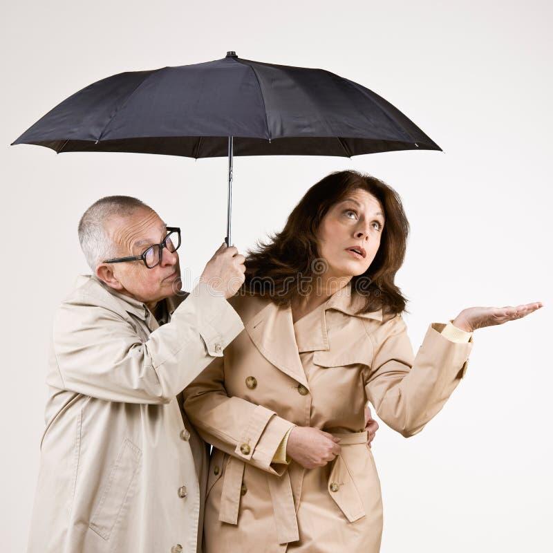 Ongerust gemaakte vrienden in regenjassen onder paraplu stock afbeeldingen