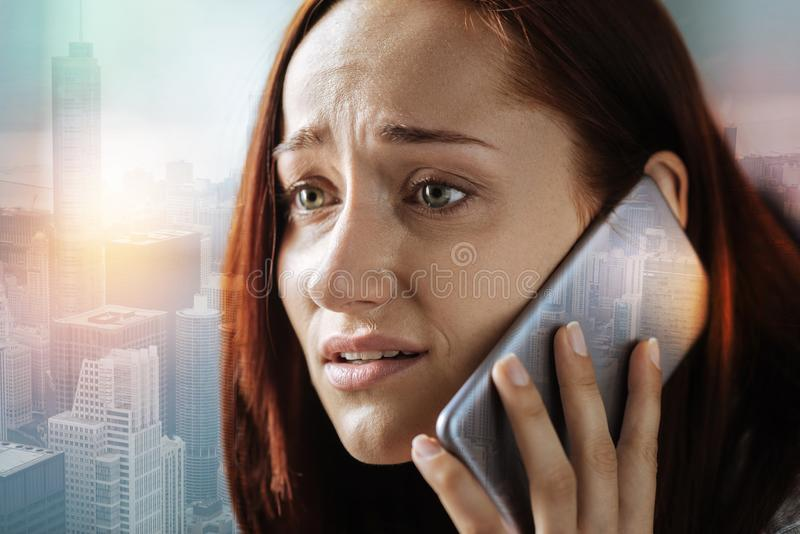 Ongerust gemaakte vrouw die doen schrikken terwijl het spreken op de telefoon kijken royalty-vrije stock fotografie