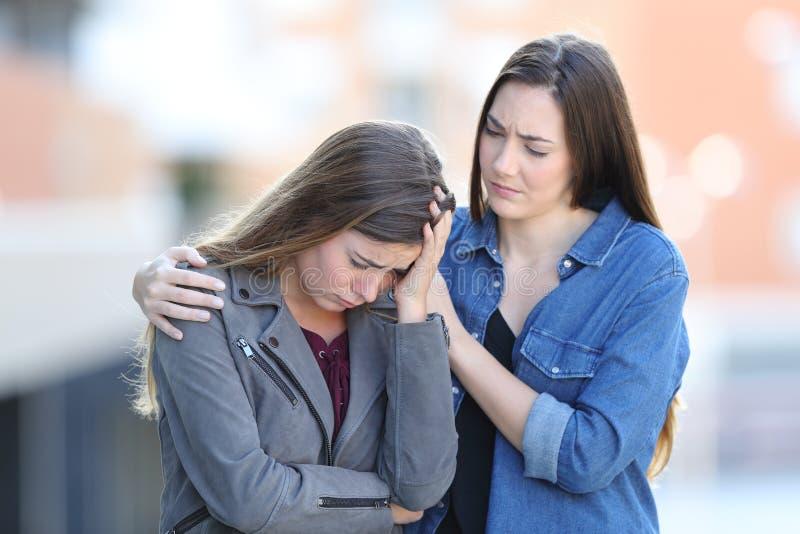 Ongerust gemaakte vrouw die haar droevige vriend in de straat troosten stock afbeelding