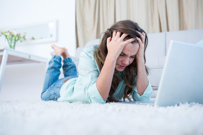 Ongerust gemaakte vrouw die haar laptop met behulp van stock afbeelding