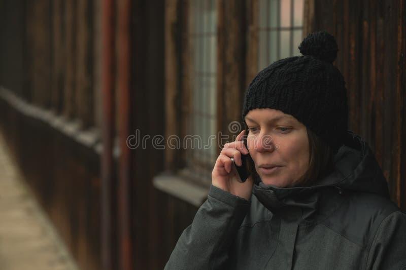 Ongerust gemaakte vrouw die op mobiele telefoon op straat spreken royalty-vrije stock fotografie