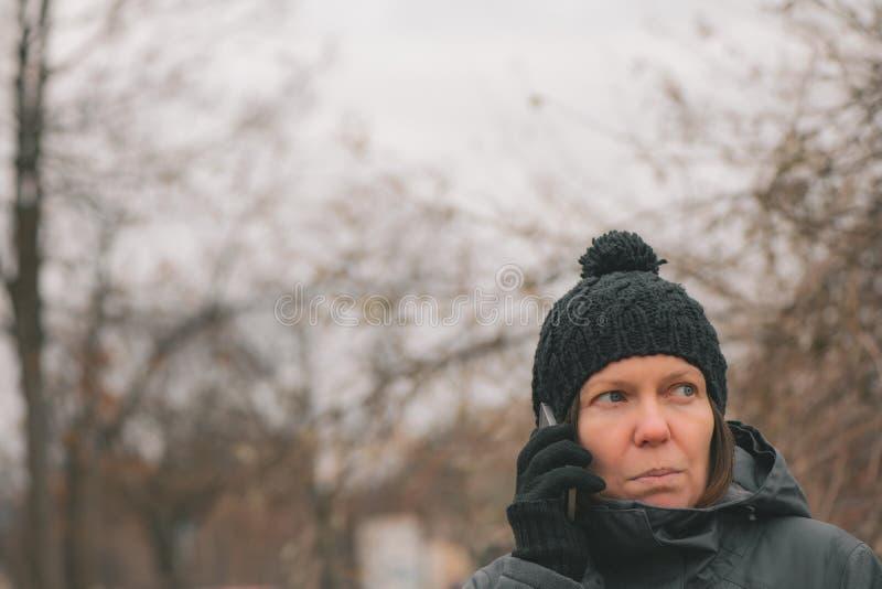 Ongerust gemaakte vrouw die op mobiele telefoon op straat spreken royalty-vrije stock afbeelding