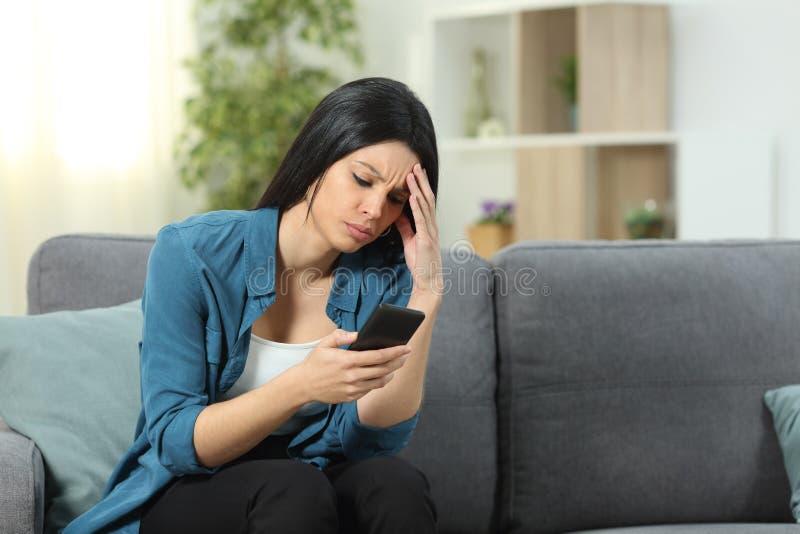 Ongerust gemaakte vrouw die smartphoneinhoud thuis controleren stock fotografie