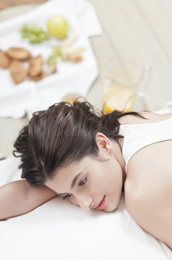 Ongerust gemaakte vrouw op bed met voedsel in de rug royalty-vrije stock foto's