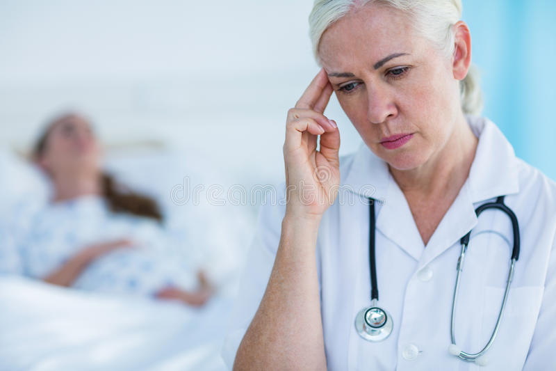 Ongerust gemaakte vrouwelijke arts die weg terwijl haar het geduldige rusten kijken stock foto