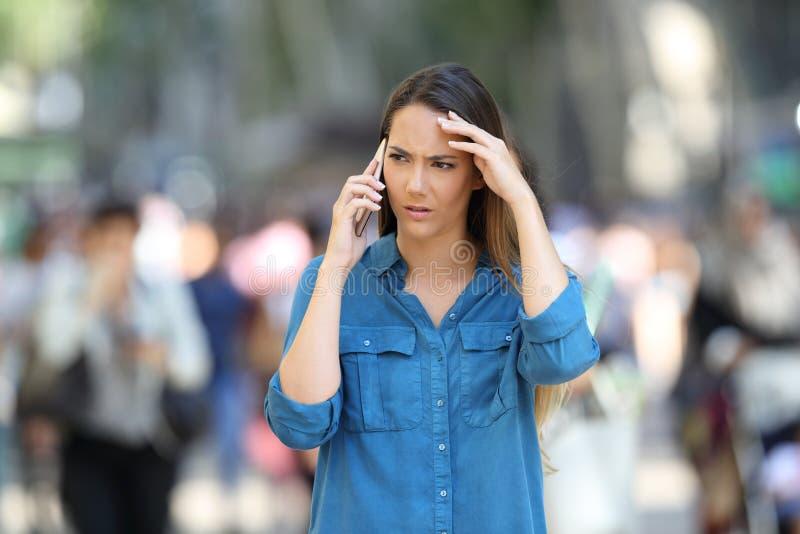 Ongerust gemaakte vrouwenbesprekingen op de telefoon in de straat stock afbeelding