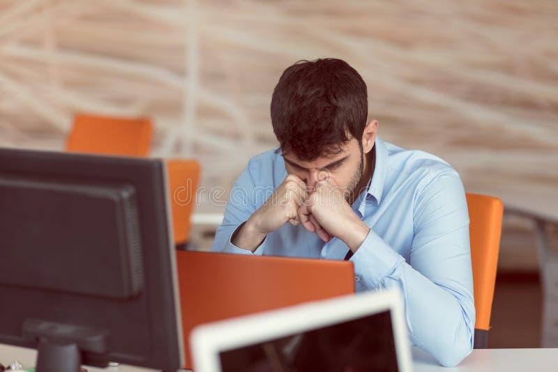 Ongerust gemaakte zakenman die bij zijn bureau in zijn bureau werken stock fotografie