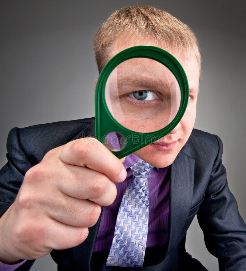 Ongerust gemaakte zakenman die door meer magnifier lens kijkt stock afbeeldingen