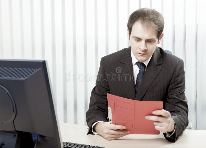 Ongerust gemaakte zakenman die een document lezen bij zijn bureau stock afbeeldingen