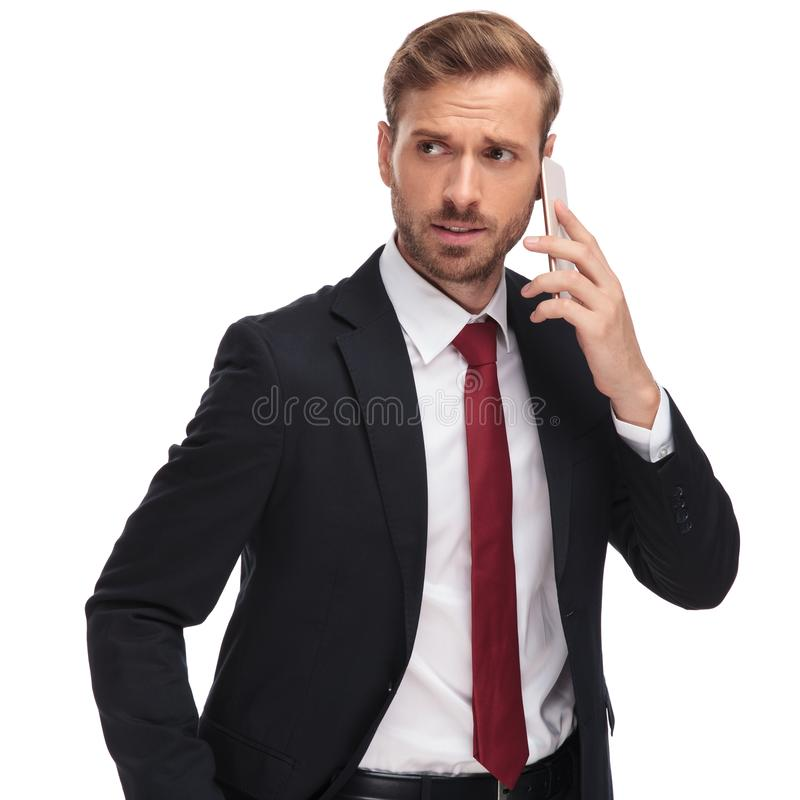 Ongerust gemaakte zakenman die op de telefoon spreken en aan kant kijken royalty-vrije stock afbeeldingen