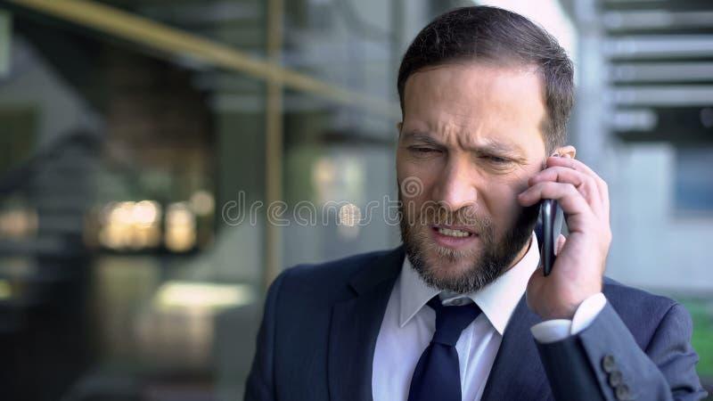 Ongerust gemaakte zakenman die op telefoon, die over zijn faillissement, problemen spreken te weten komen royalty-vrije stock foto's