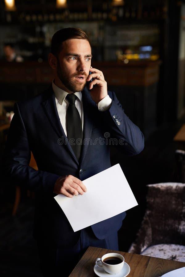 Ongerust gemaakte zakenman die op telefoon in restaurant spreken royalty-vrije stock foto's