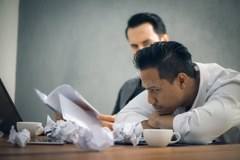 Ongerust gemaakte zakenman in donkere kostuumzitting bij bureauhoogtepunt met boeken en documenten die met het werk worden overbe stock foto