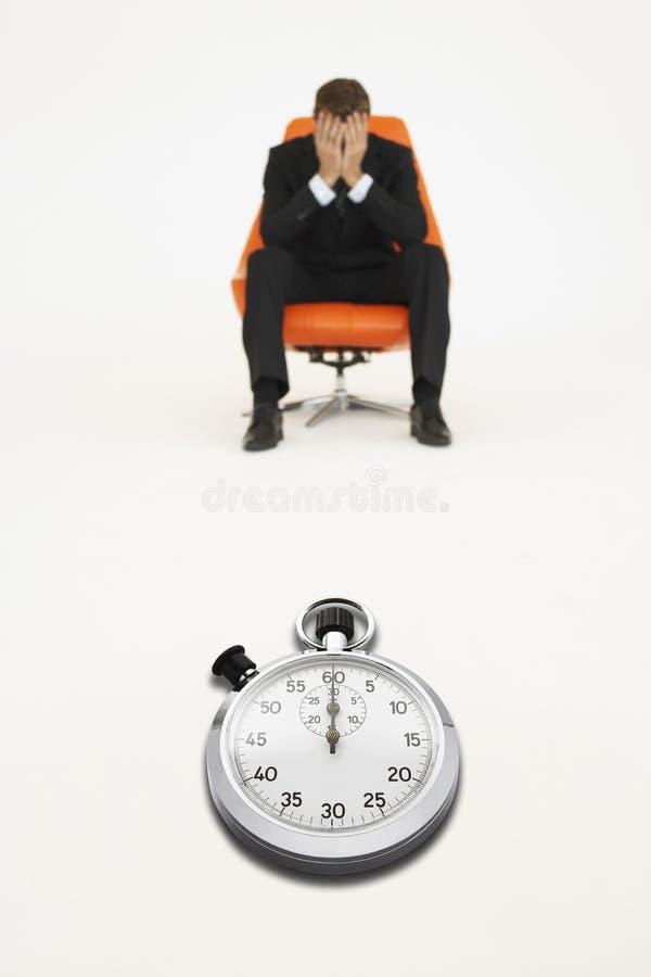 Ongerust gemaakte zakenmanzitting op stoel met chronometer die verlies van tijd vertegenwoordigen stock foto's
