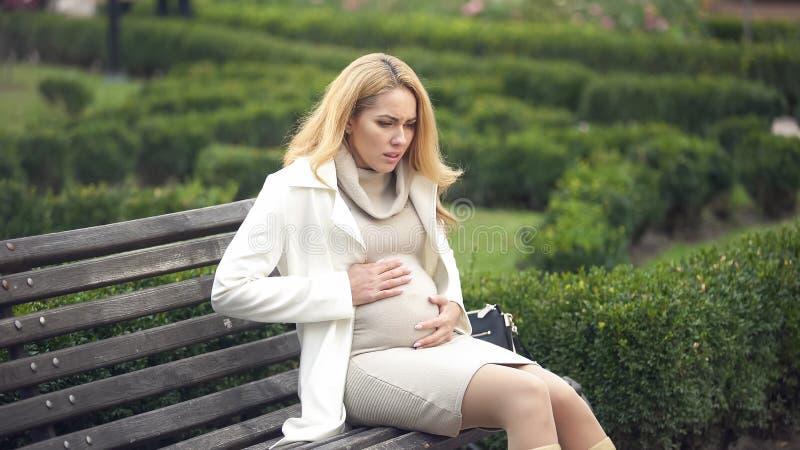 Ongerust gemaakte zwangere dame die, het zitten bank, buikpijn, samentrekkingen diep ademen stock foto