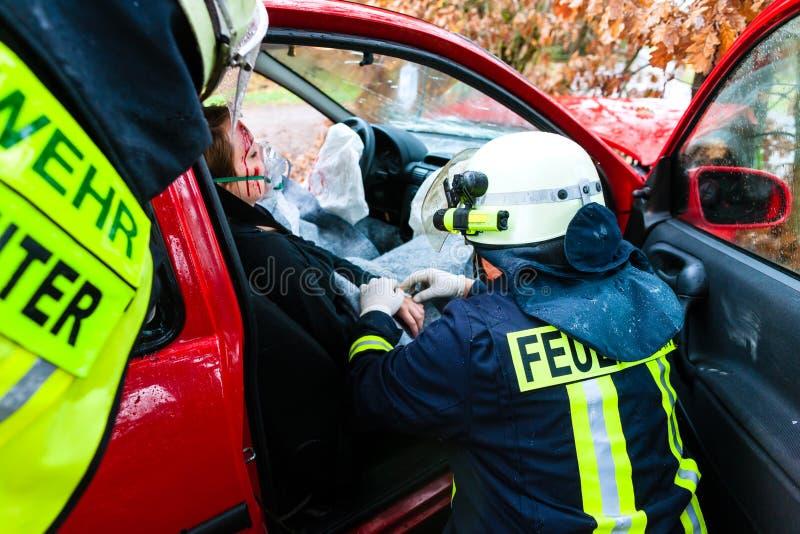 Ongeval - de reddingenslachtoffer van de Brandbrigade van een autoneerstorting stock foto