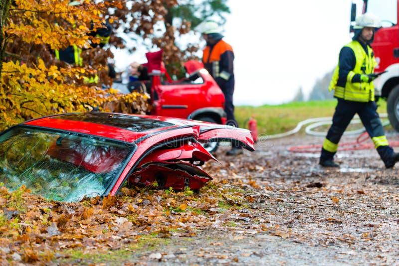 Ongeval - het Slachtoffer van de brigadereddingen van de Brand van een auto stock afbeeldingen