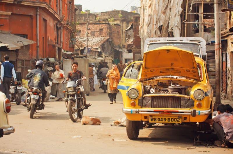 Ongeval met een auto op een bezige straat met voetgangers en fietsers van stoffige stad stock afbeeldingen